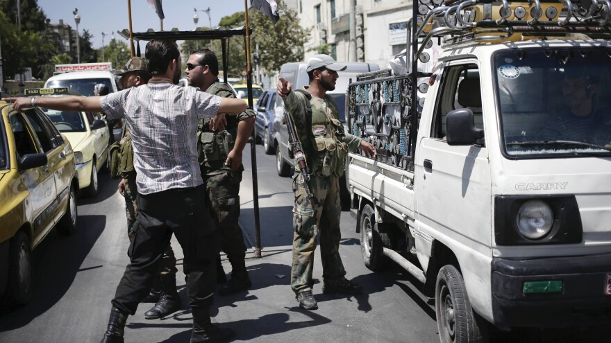 Syrian military soldiers check identifications and search vehicles at a checkpoint on Baghdad Street in Damascus, Syria, on Aug. 21.