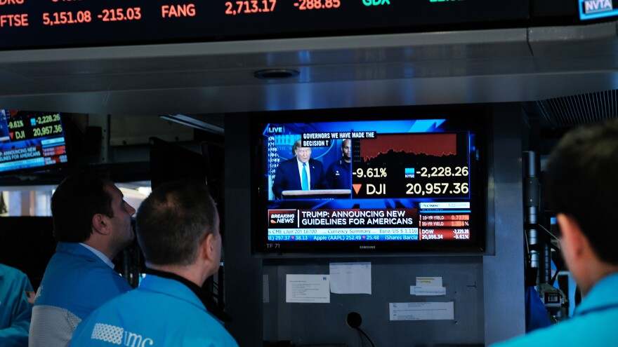Traders on the floor of the New York Stock Exchange watch as Trump makes his announcement. A week later, the floor shut down because of the virus, and trade moved fully to electronic systems.