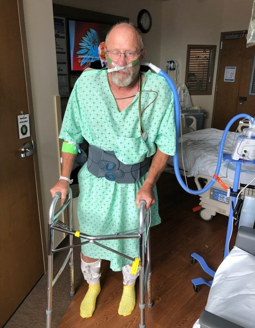 Chad Larsen, Wootton's father, stands for the first time in over a month. Larsen contracted COVID-19 after he was initially hospitalized for something else.