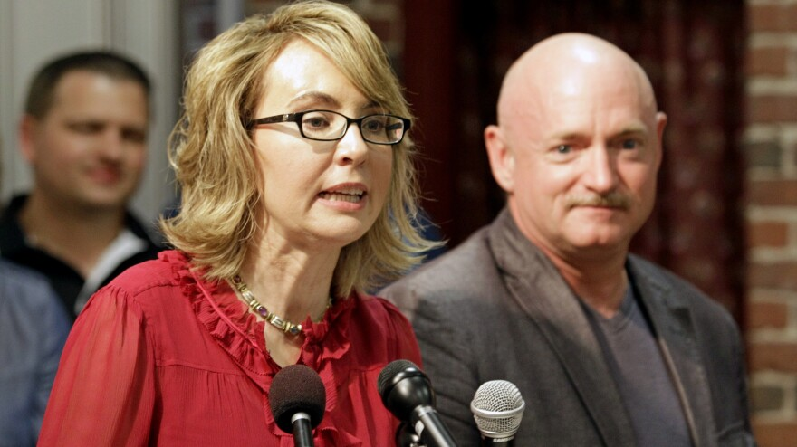 Former Arizona Rep. Gabrielle Giffords, accompanied by her husband, retired astronaut Mark Kelly, speaks during a July 2013 news conference in Manchester, N.H.
