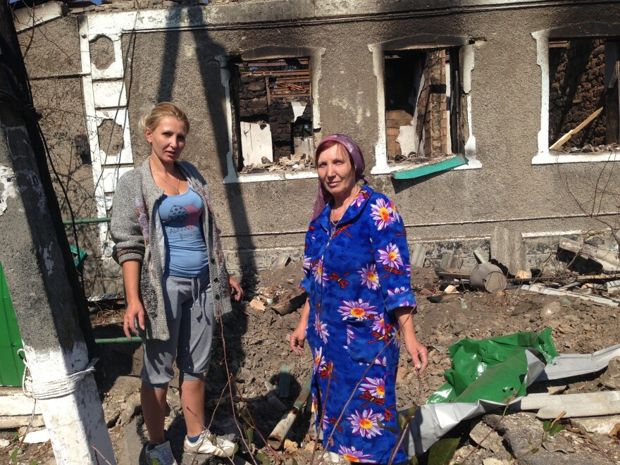 "Svetlana Duginova and her daughter Klaudia Fedorashko pick through the rubble of Duginova's parents' house in the shelled village of Novokaterinovka. ""We are all so tired of this,"" they say."