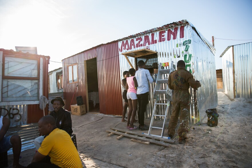 A man paints the newly opened Mazaleni tuck shop in Covid. It sells a mix of products, from soap to matches to chips. In the foreground men drink at a outdoor shabeen — an unlicensed bar.