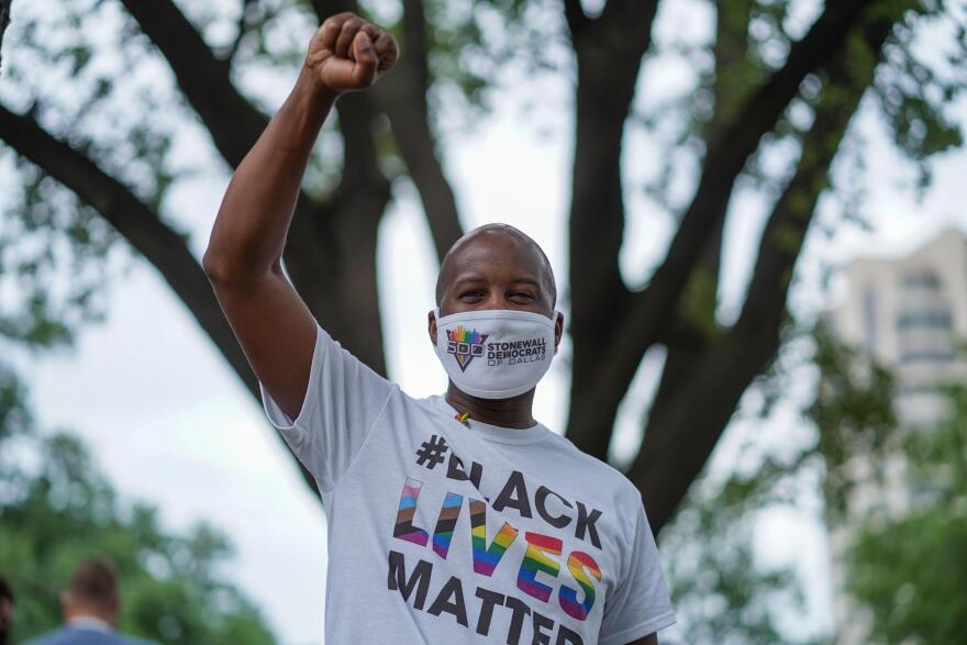 Brandon J. Vance thrusts a fist into the air while wearing a Black Lives Matter shirt. He's a U.S. Air Force veteran and president of the Stonewall Democrats of Dallas.