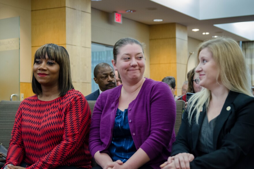 St. Louis Board of Education President Dorothy Rohde-Collins, center, smiles at school board member Natalie Vowell following a vote to reinstitute the board's control of St. Louis Public Schools. Board member Susan Jones is at left. April 16, 2019.