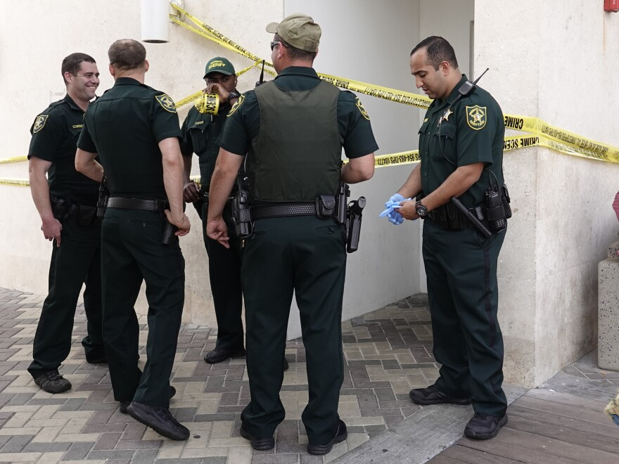 Broward Sheriff's deputies surround a men's bathroom at the Deerfield Beach pier in Florida, where a loaded gun was found — after fired — on Sunday.