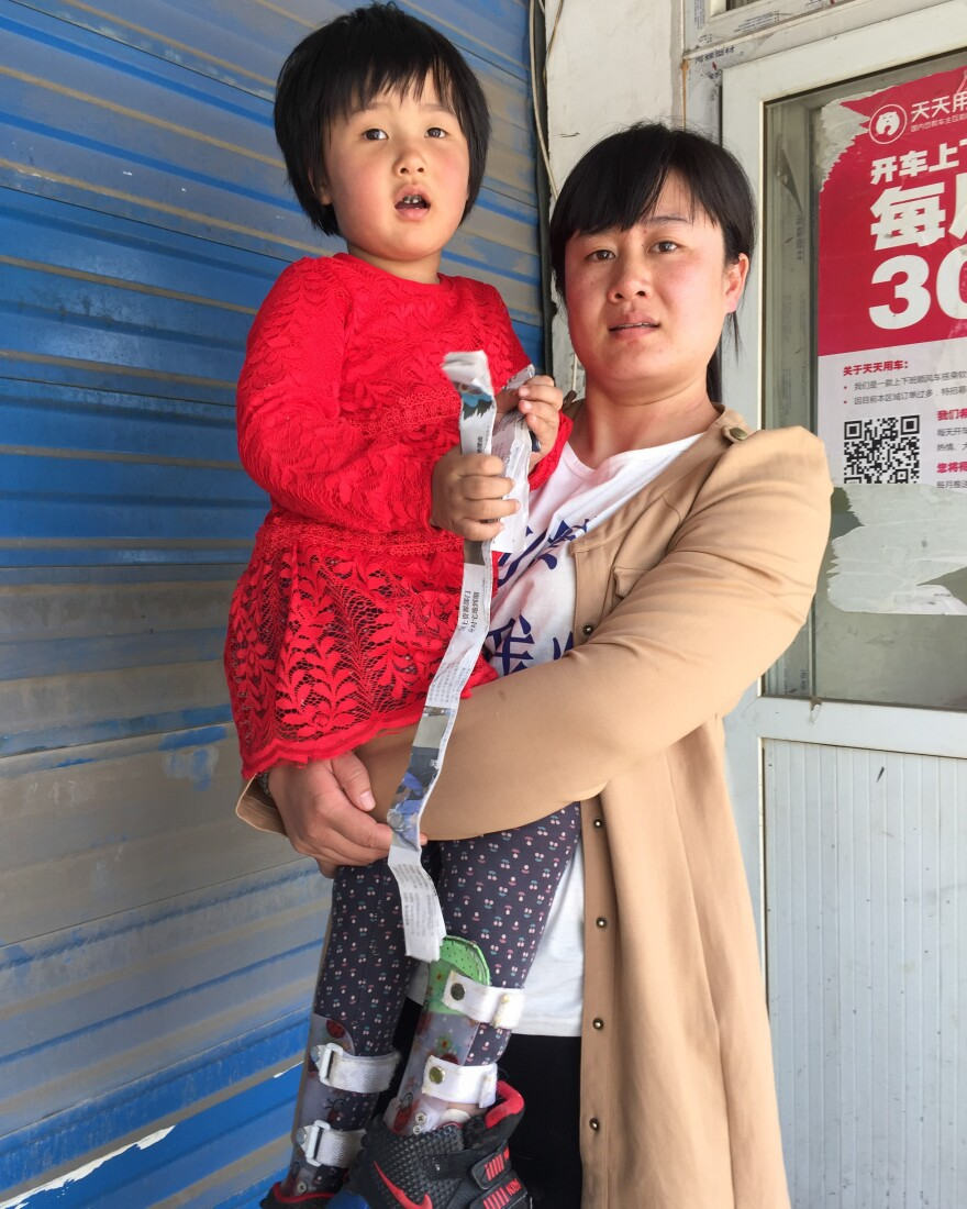 Dong Xiaoxin carries her daughter Yin Jiayue as she protests outside government health authority offices in Beijing. The child was stricken by polio even though her parents say she received a government-administered polio vaccine.