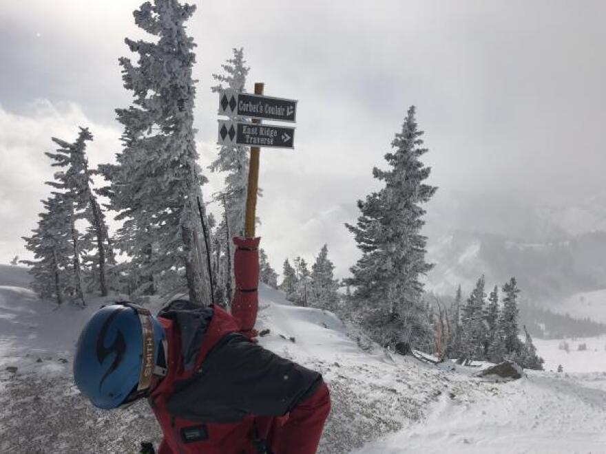 Trey Scharp, a Teton Mountain ski instructor, stands in front of the sign for the legendary Corbet's Couloir run on top of the mountain.