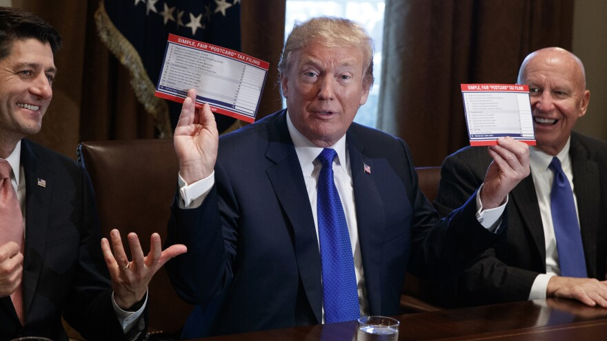 President Trump holds an example of what a new tax form may look like during a tax-policy meeting at the White House with Republican lawmakers.
