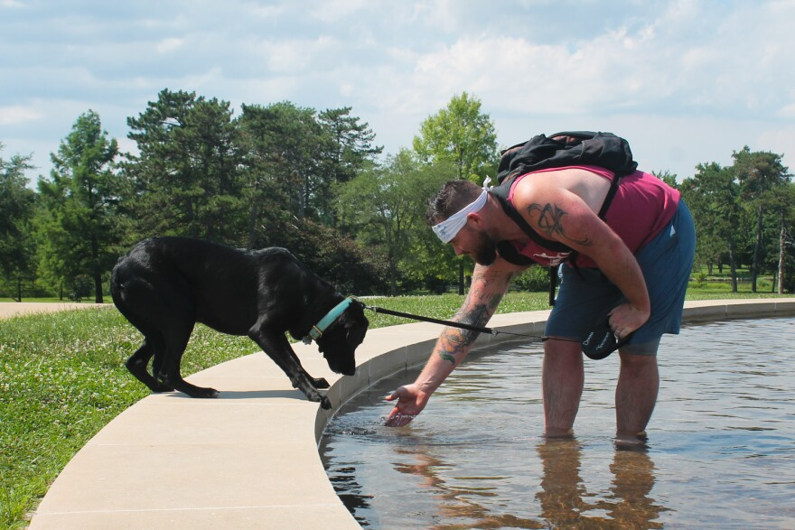 Tony Bartleson attemps to lure his dog, Murphy, into the water at Kerth Fountain in Forest Park on Thursday, July 5, 2018.