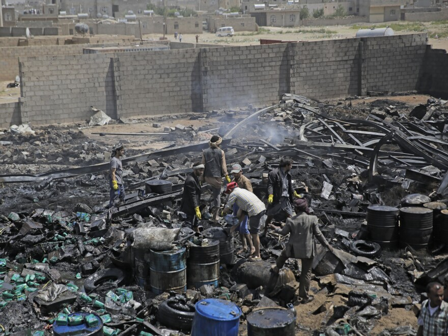 Workers salvage oil canisters from the wreckage of a vehicle oil store hit by Saudi-led airstrikes last July in Sanaa, Yemen. The U.S. said Thursday it will no longer back the Saudi-led military offensive.