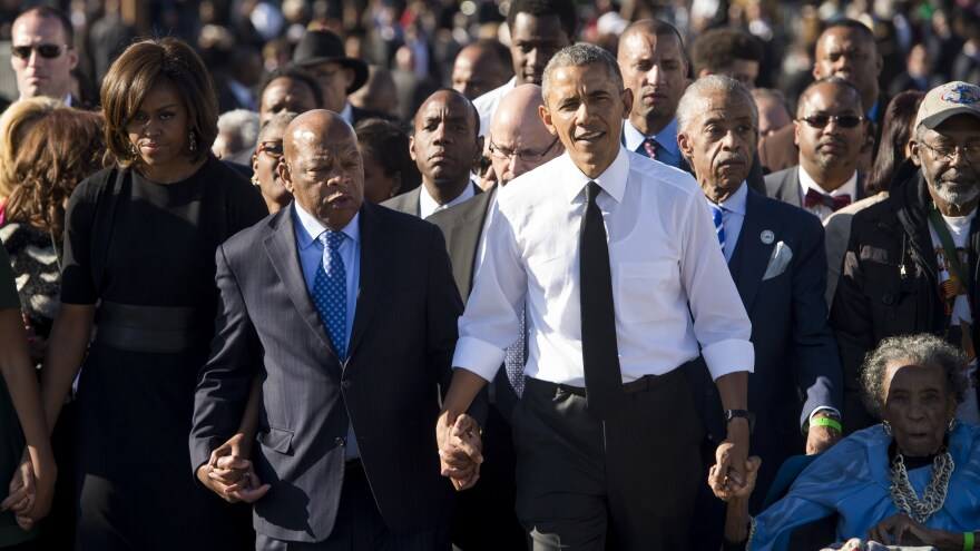 Obama and Rep. John Lewis walk across across the Edmund Pettus Bridge to mark the 50th anniversary of the Selma to Montgomery civil rights marches in Selma, Ala.