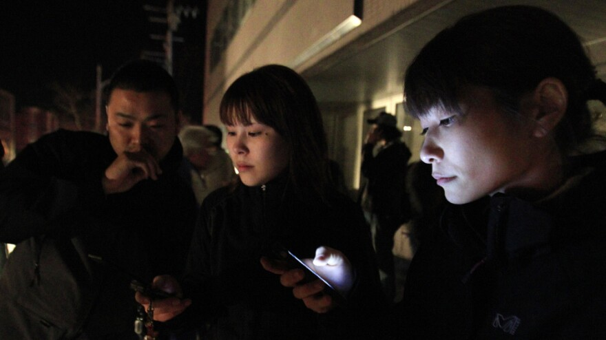 Hotel guests in Ichinoseki, Iwate prefecture, checked their mobile phones for news after they ran outside following a major earthquake that hit Japan on Thursday night.