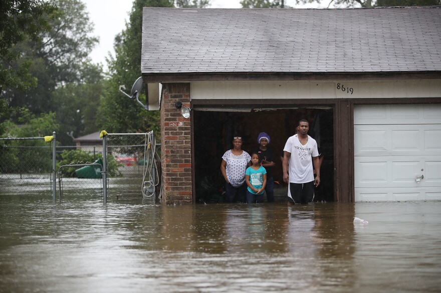 People wait to be rescued from their home after the area was inundated from Hurricane Harvey in Houston on Monday. President Trump travels to Texas on Tuesday.