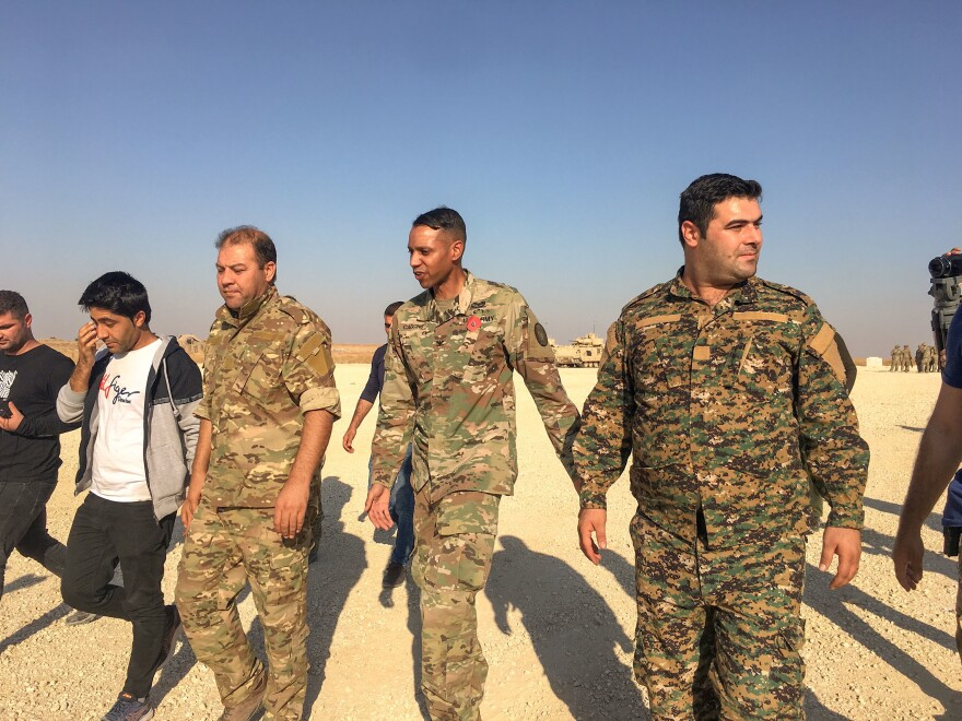 Mustafa Bali (left) and Kino Gabriel (right) walk with U.S. military spokesman Myles Caggins III (center). It's the first time that Bali and Gabriel, the spokesmen for the Kurdish-led Syrian Democratic Forces, have met a U.S. military spokesman in five years.