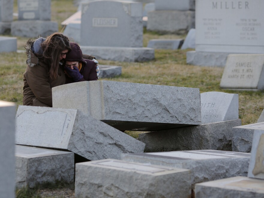 Melanie Steinhardt comforts Becca Richman at the Jewish Mount Carmel Cemetery in Philadelphia. Police say more than 100 tombstones were vandalized a week after a Jewish cemetery in St. Louis was also desecrated.