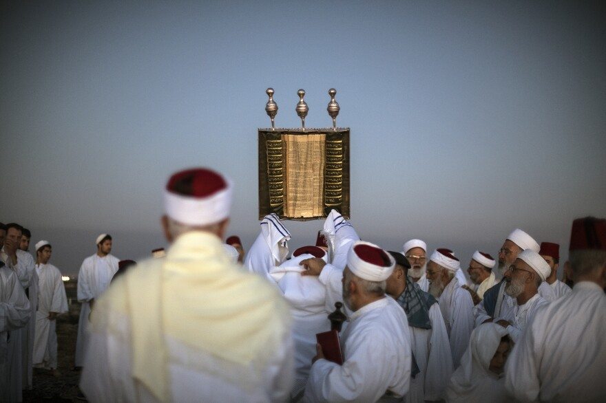 A priest lifts a Samaritan Torah scroll during sunrise prayers on Mount Gerizim in the West Bank. One of the world's oldest and tiniest sects, the Samaritans trace their roots to the ancient Israelites.