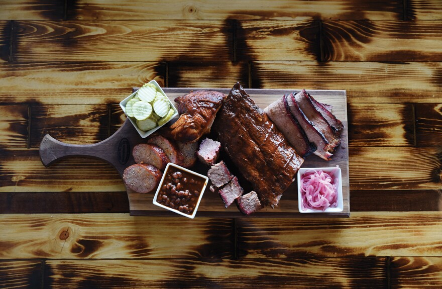 Picture of a cutting board displaying various cuts of meat and side dishes