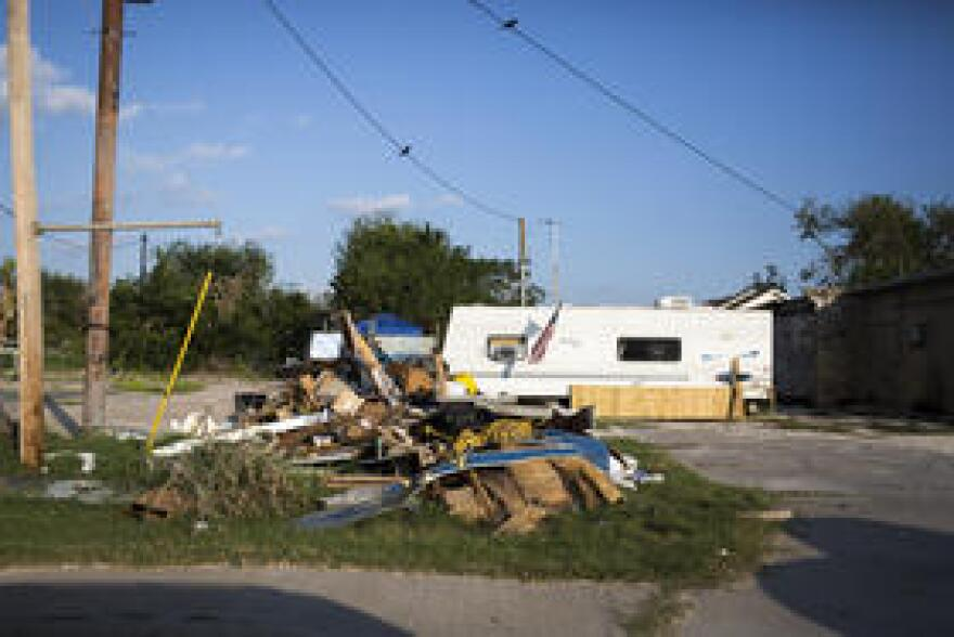 Debris is piled in front of a property along Highway 77 in Refugio.