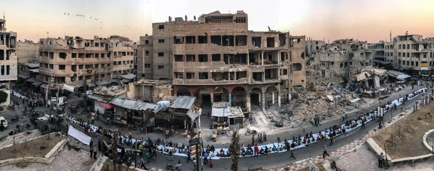 During a lull in the bombings, Syrians in the city of Douma gather for the evening meal at the end of a Ramadan fast.