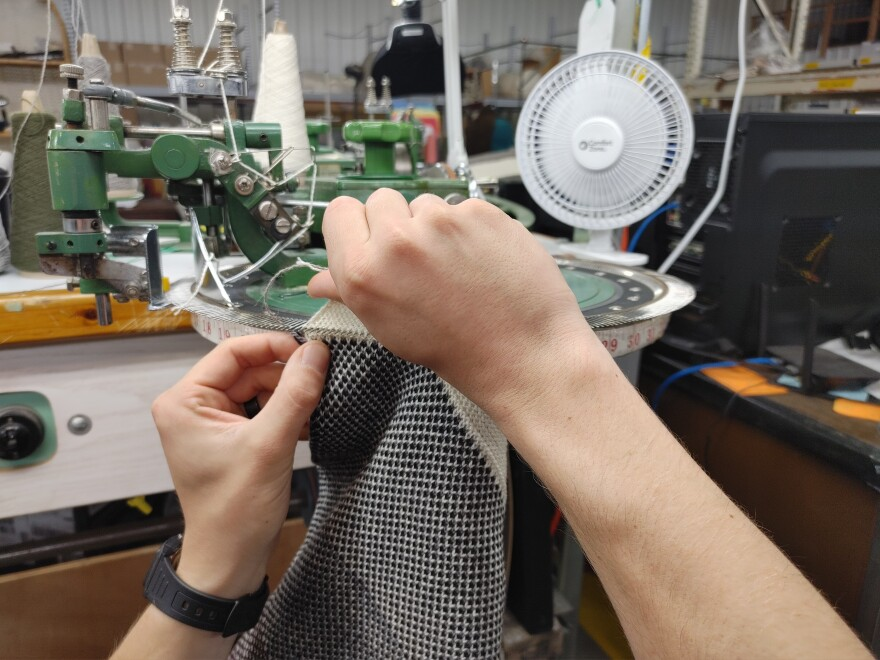 A mini sewing machine is connected to a large round wheel with large needles on the edge.  Someone is putting the threads of a blanket on the needles.
