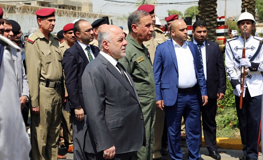 Iraqi Prime Minister Haider al-Abadi (center) attends a funeral for two generals killed in fighting with Islamic State militants in Ramadi, west of Baghdad, in August. In an interview Monday with NPR, the Iraqi leader called on the U.S. to provide more airstrikes but said his country does not want ground forces from the U.S. or any other country.