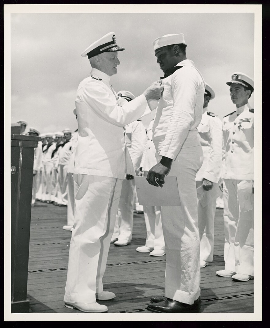 Admiral Chester W. Nimitz, Commander-in-Chief of the U.S. Pacific Fleet, pins the Navy Cross on Miller at a ceremony on board a U.S. Navy warship in Pearl Harbor on May 27, 1942.