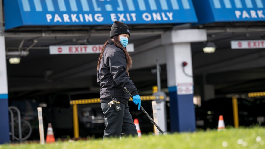 A Pier 39 employee wears protective gear while cleaning a sidewalk in San Francisco, Calif., on March 16, the day the county announced a local shelter-in-place order. On March 19, California Gov. Gavin Newsom announced a shelter-in-place order for the entire state.