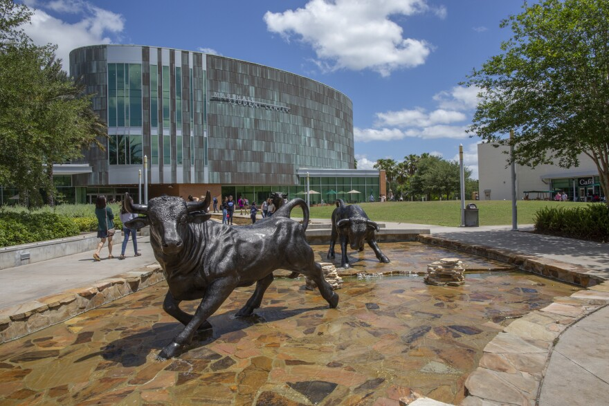 Bronze bull statues in the fountain in front of a green copper looming student center.