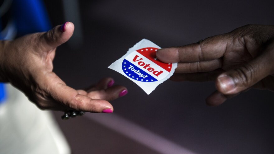 "A poll worker hands out ""I Voted Today"" stickers in Washington, D.C., in 2012. Journalist Ari Berman says a 2013 Supreme Court ruling opened the door for new voting restrictions that  disproportionately affect poor people, young people and people of color."