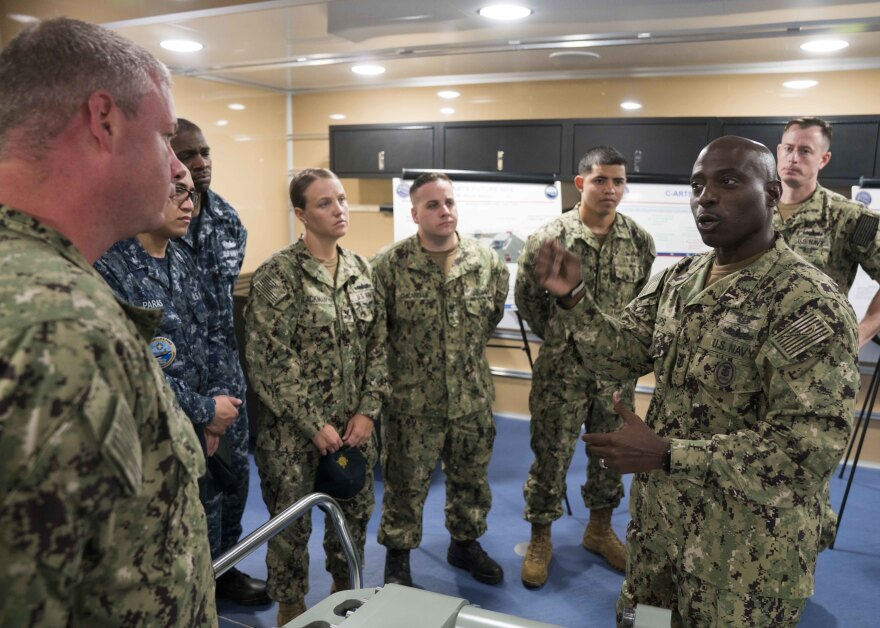 Commander, Naval Air Force Atlantic Force Master Chief Huben Phillips (right) speaks to Sailors from the aircraft carrier USS Gerald R. Ford after a Carrier-Advanced Reconfigurable Training Systems presentation in 2018.