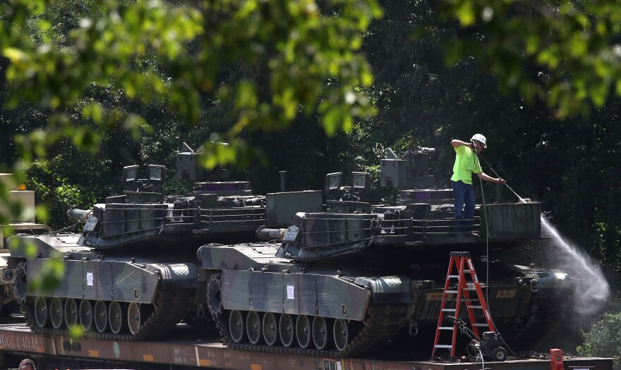 A worker washes Abrams tanks that are loaded on railcars in Washington, D.C., on Tuesday.