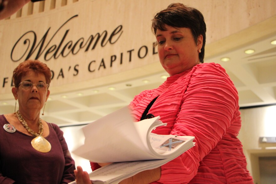 Amy Weintraub (right) with Progress Florida shows a petition, signed by 5,500 Floridians, calling for the Department of Health to tighten regulations on crisis pregnancy centers. Weintraub delivered it to the desk of Gov. Rick Scott.
