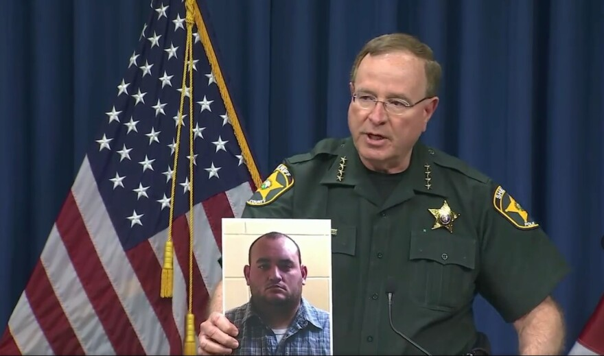 Polk Sheriff Grady Judd holds a mug shot of Deputy Peter Heneen