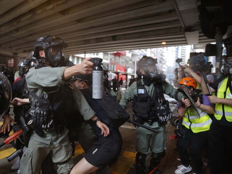 Riot Police use pepper spray on protesters during a protest against Beijing's national security legislation in Causeway Bay in Hong Kong, Sunday. Hong Kong police fired volleys of tear gas in a popular shopping district as hundreds took to the streets Sunday to march against China's proposed tough national security legislation for the city.