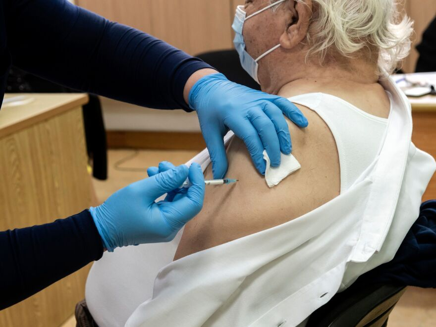 A healthcare worker administers a dose of the coronavirus vaccine to an elderly at a health center in the Cypriot coastal city of Limassol on February 8, 2021.