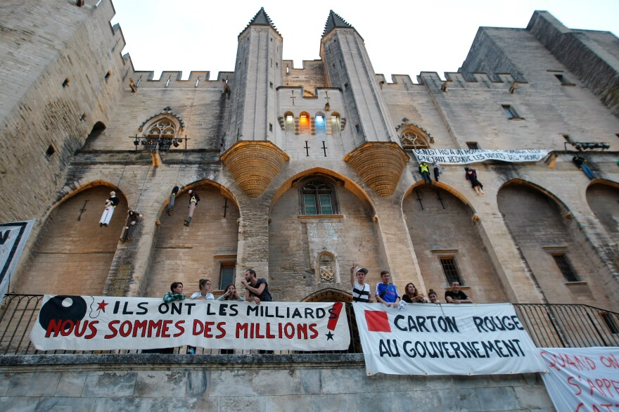 """Protest banners outside Avignon's Palais des Papes read: """"They have billions, we are millions"""" (left) and """"Red card to the government."""" Festival actors and technicians have been striking over talk of changes to their off-season unemployment benefits."""