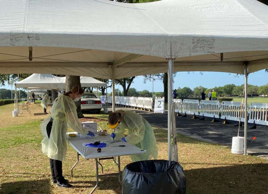Two gowned and masked researchers doing testing on table under tent