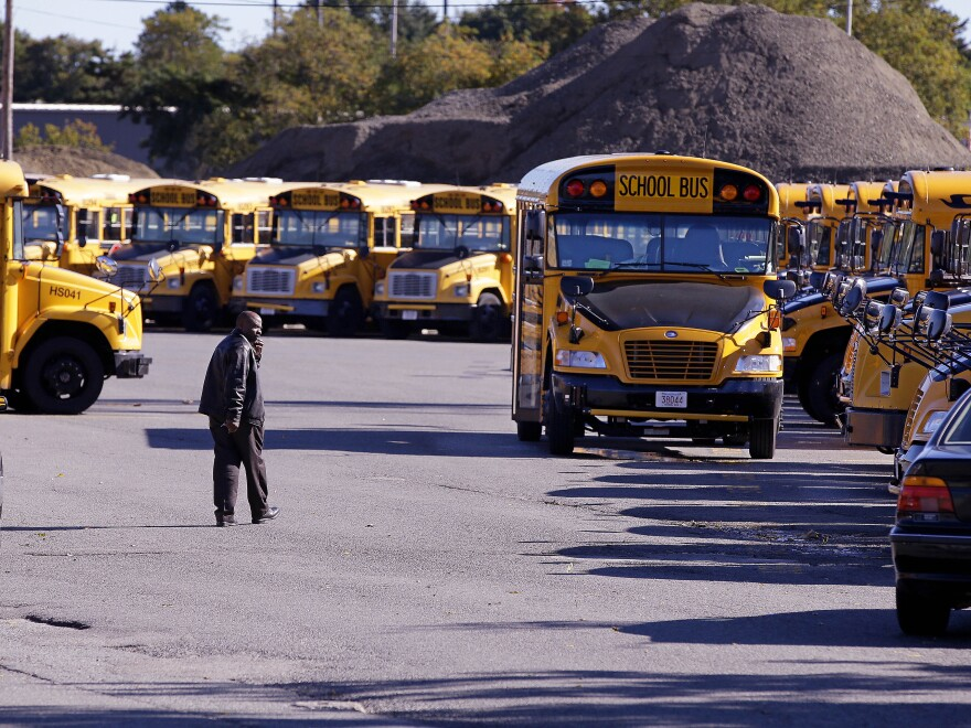 A man in a jacket walking towards school buses parked in a big lot in rows.