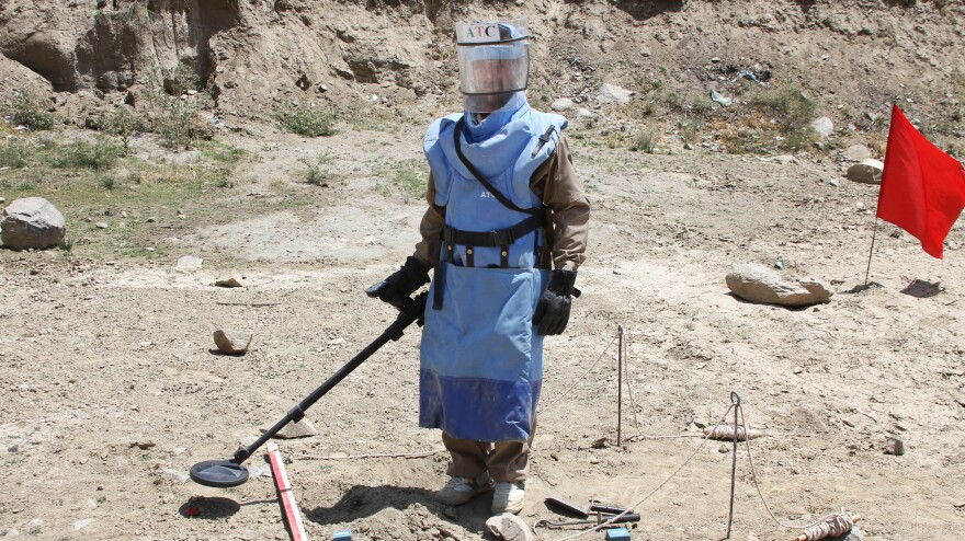 A de-mining expert demonstrates how to find land mines in a training area near Hakim Village in central Afghanistan, where Soviet mines dating to the 1980s are still a danger.