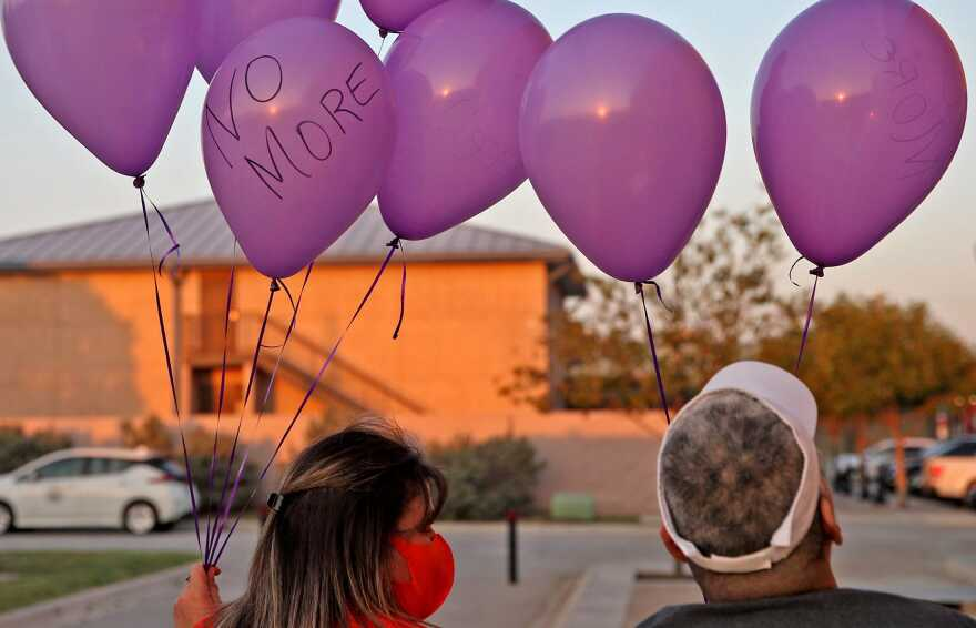 A group gathers to release balloons during the first scheduled event honoring National Domestic Violence Awareness Month in San Angelo.