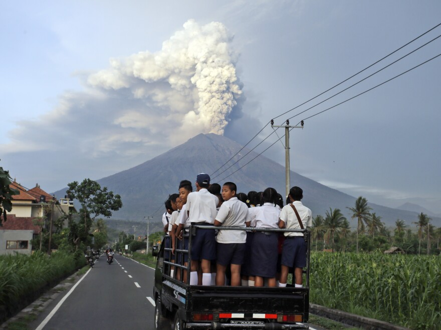 Students stand on a truck as they head to school with Mount Agung volcano spewing smoke and ash in Karangasem, Bali, Indonesia, on Tuesday.