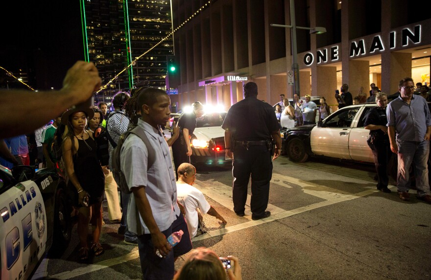 Police attempt to calm the crowd as someone is arrested near the scene of the sniper shooting in Dallas on Thursday.