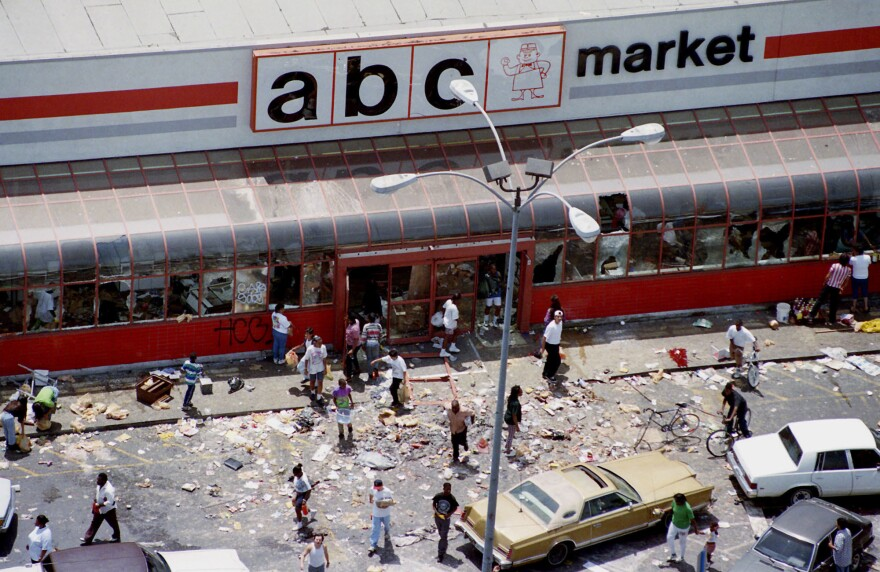 People walk in the parking lot of the ABC Market after it was looted in Los Angeles on April 30, 1992.