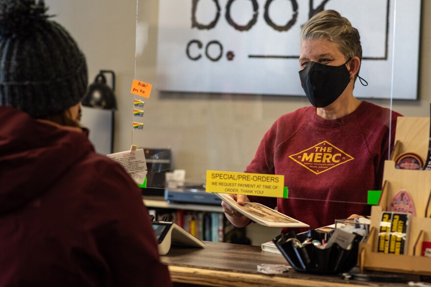 Chelsia Rice wears a face mask and hands a magazine to a customer underneath a plexiglass shield.