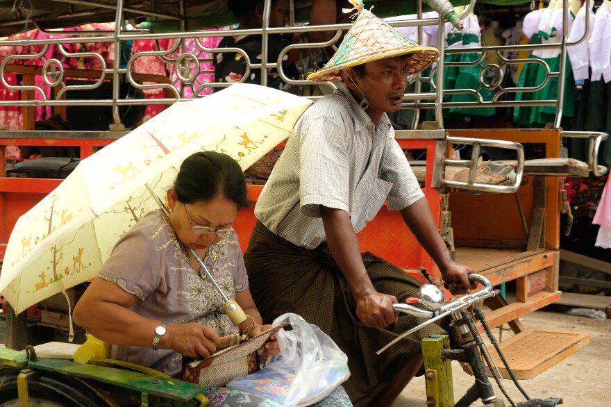 A rickshaw driver and passenger travel in Sittwe, the capital of Myanmar's Rakhine State. The conflict in the state is between two minority groups, the Buddhist Rakhine and the Muslim Rohingya. Both have faced different degrees of persecution during decades of military rule from 1962 to 2016.