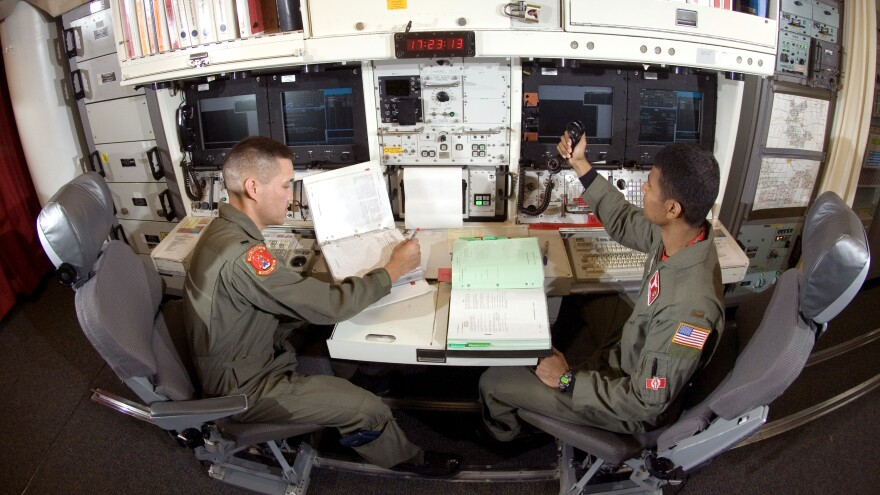 A missile combat crew sits in an underground launch control bunker at Minot Air Force Base in North Dakota. Officers must use checklists for everything they do. They are tested three times a month.