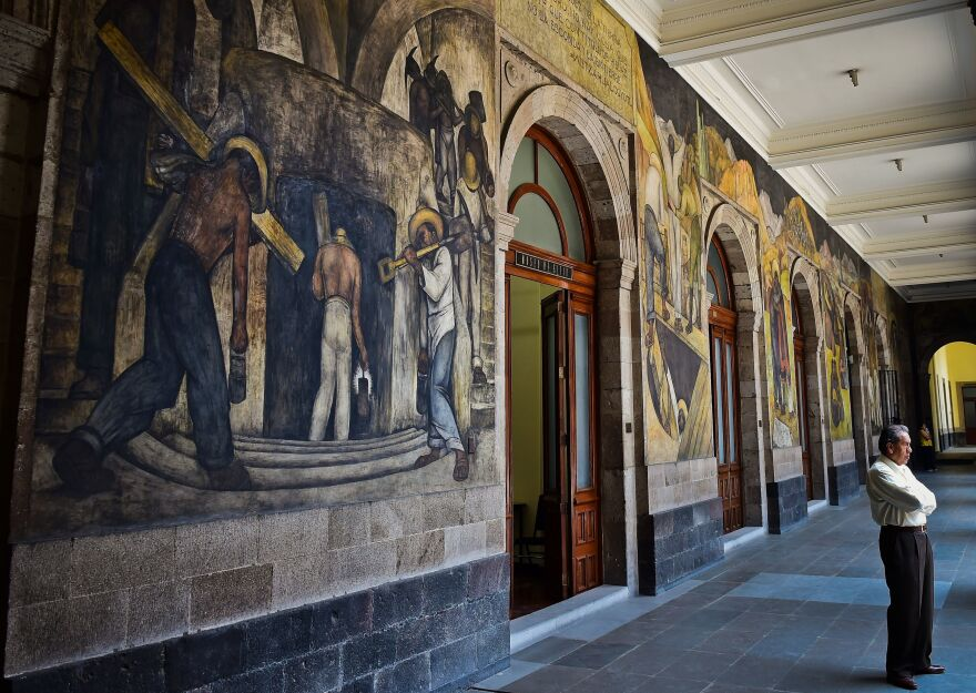 A man stands next to murals by Diego Rivera in the Education Secretariat in Mexico City in April 2017.