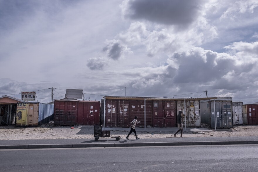 Boys walk past shuttered businesses in the township of Khayelitsha, Cape Town, South Africa, during the country's coronavirus lockdown.