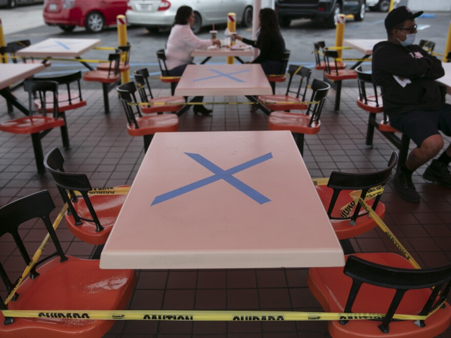 Tables are marked with X's for social distancing in the outdoor dining area of a restaurant in Los Angeles, Wednesday. California Gov. Gavin Newsom has ordered a three-week closure of bars and indoor operations of restaurants and certain other businesses in Los Angeles and 18 other counties as the state copes with increasing cases of COVID-19.
