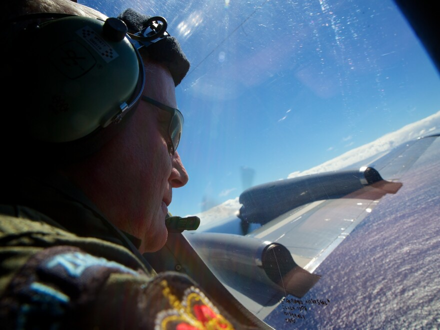 "Sgt. Trent Wyatt, a crew member of a Royal New Zealand Air Force P-3 Orion, looks out in the search for MH370 over the Indian Ocean in April of last year. A Malaysian official says the search will continue through the end of May 2015, but if nothing is found, it is ""back to the drawing board."""